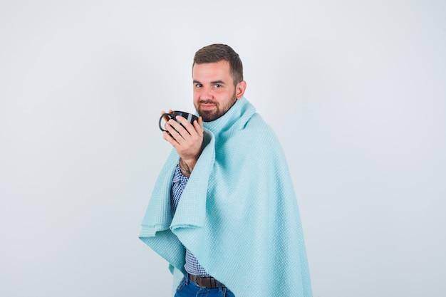 Homem bonito na camisa, jeans, xale, segurando uma xícara de chá com as duas mãos e olhando feliz, vista frontal.