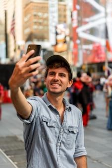 Homem bonito na cidade tomando selfie
