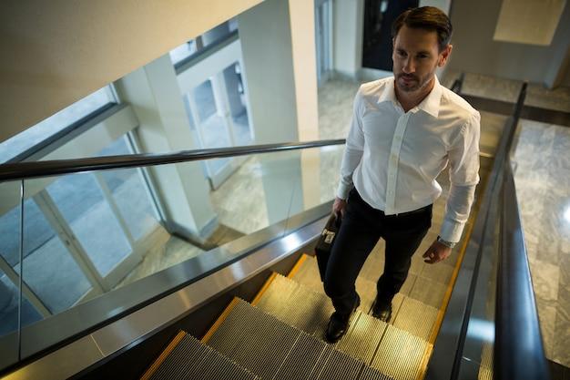 Homem bonito na escada rolante