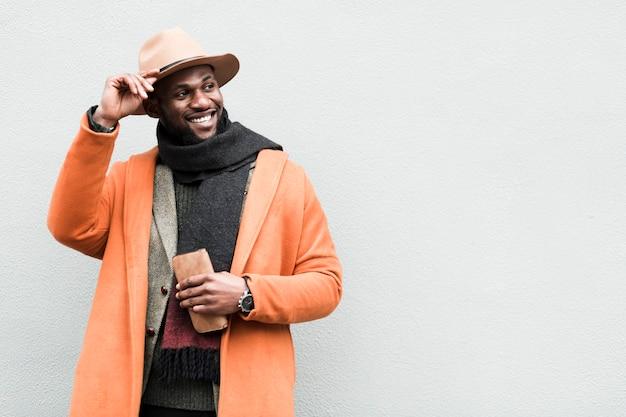 Homem bonito na jaqueta laranja posando com espaço de cópia