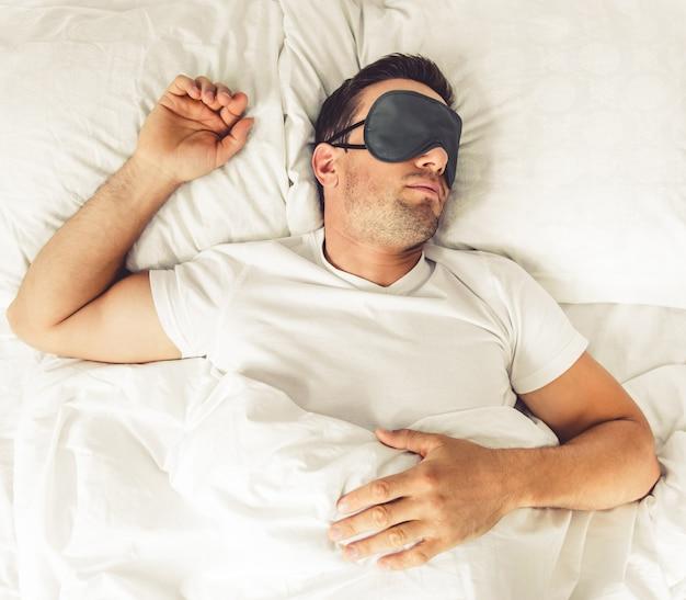 Homem bonito na máscara de dormir em sua cama