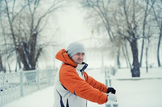 Homem bonito na neve do inverno