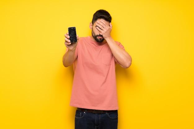 Homem bonito na parede amarela com incomodado segurando smartphone quebrado