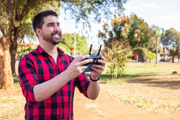 Homem bonito na praça pilotando um drone. menino com o controle remoto filmando com o drone.