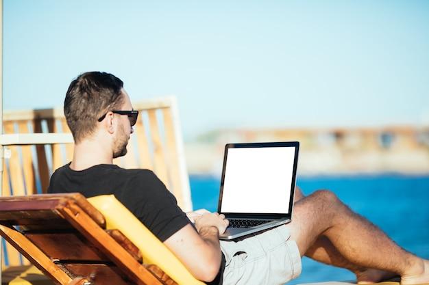Homem bonito na praia digitando em seu laptop com tela branca para copyspace enquanto está sentado em sua espreguiçadeira