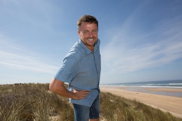 Homem bonito na praia sob o céu azul