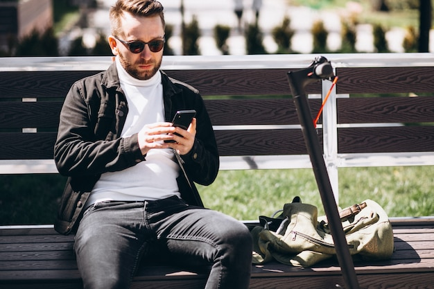 Homem bonito na scooter, compras on-line no telefone