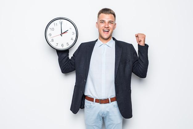 Homem bonito na suíte segurando um grande relógio em uma das mãos, isolado no branco