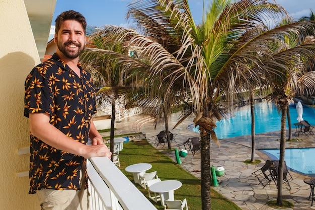 Homem bonito na varanda do hotel