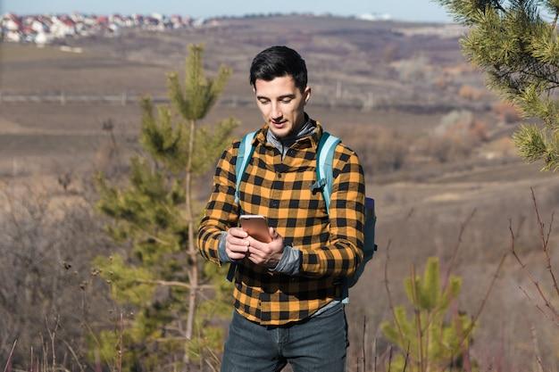 Homem bonito na zona rural, usando o telefone para navegar