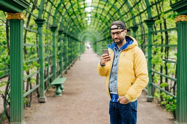 Homem bonito no boné da moda, jeans e anoraque amarelo usando óculos, segurando a mão no bolso