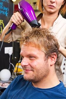 Homem bonito no cabeleireiro secando o cabelo
