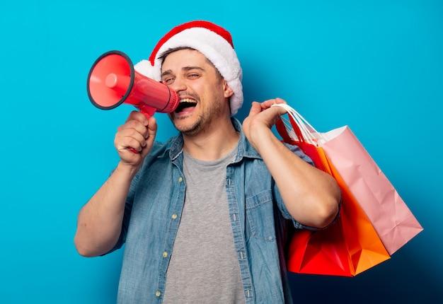 Homem bonito no chapéu de natal com alto-hailer e sacolas de compras
