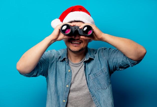 Homem bonito no chapéu de natal com binóculos