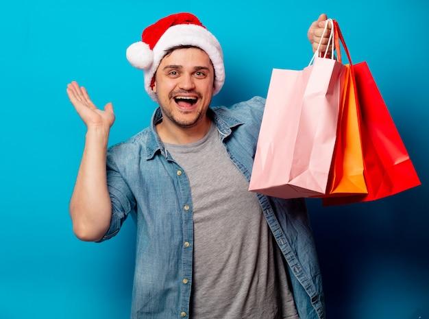 Homem bonito no chapéu de natal com sacos de compras
