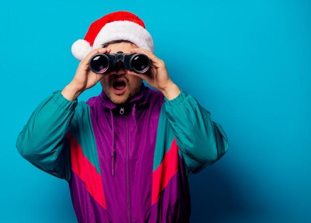 Homem bonito no chapéu de natal e jaqueta dos anos 90 com binóculos