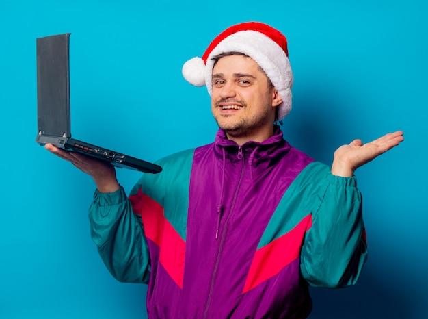 Homem bonito no chapéu de natal e jaqueta dos anos 90 com laptop