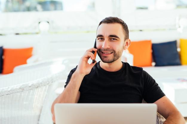 Homem bonito no convés com telefone celular e laptop na zona lounge do resort de verão