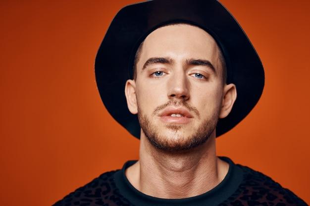 Homem bonito no estúdio de chapéu preto posando com fundo laranja