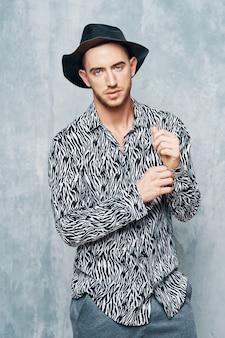 Homem bonito no estúdio de moda de camisa preta e branca posando