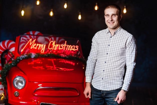 Homem bonito no estúdio de natal no contexto de luzes brilhantes e carro retrô.