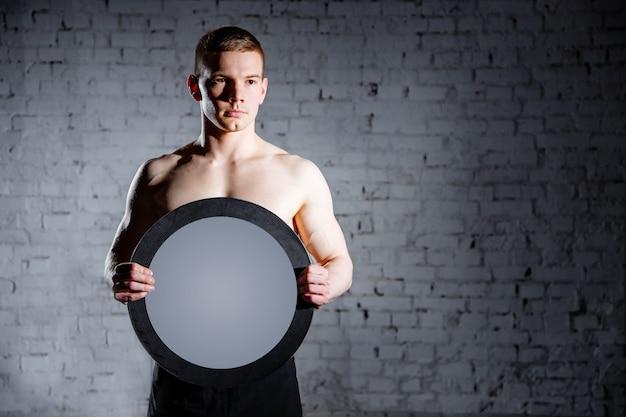 Homem bonito no ginásio o conceito de sucesso e realização de metas, resultados