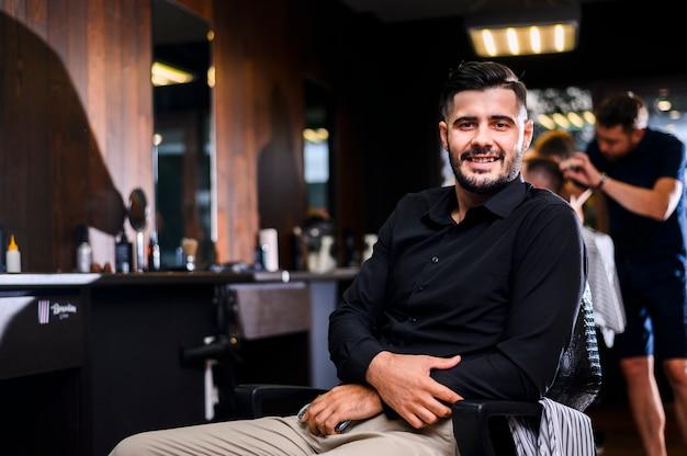 Homem bonito no salão de cabeleireiro de frente para a câmera