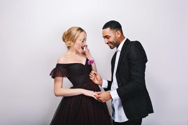 Homem bonito no smoking dando flores a uma bela jovem loira em um vestido de noite de luxo. momentos de espanto, alegria, alegria, dia dos namorados, presente, amor, juntos.
