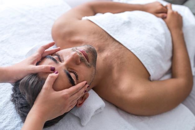 Homem bonito no spa recebendo um facial