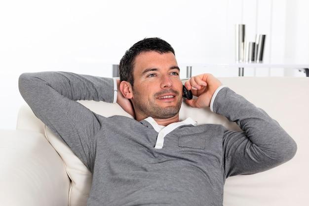 Homem bonito no telefone em casa no sofá