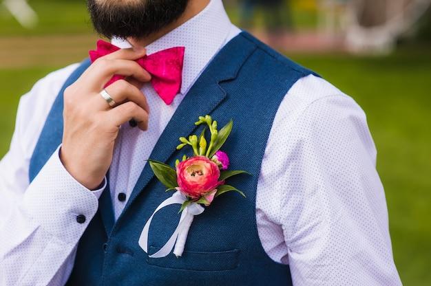 Homem bonito, noivo perto com laço rosa