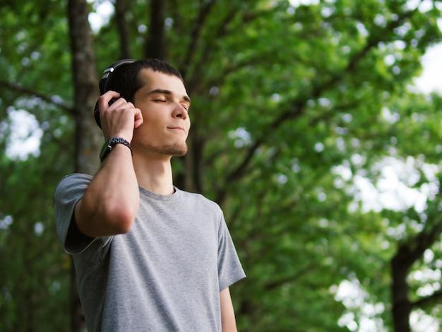 Homem bonito nos auscultadores que escuta a música ao ar livre.