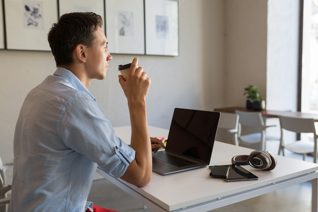 Homem bonito ocupado com seu trabalho tomando café
