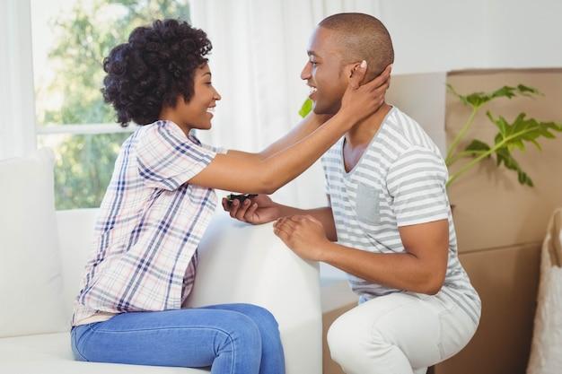 Homem bonito, oferecendo o anel de noivado para sua namorada na sala de estar