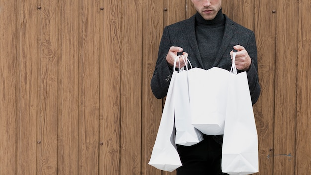 Homem bonito, olhando em sacolas de compras