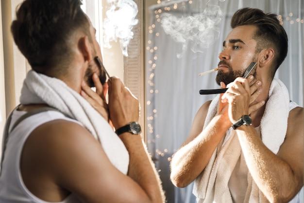 Homem bonito olhando no espelho, fumando um cigarro e raspando a barba com uma navalha