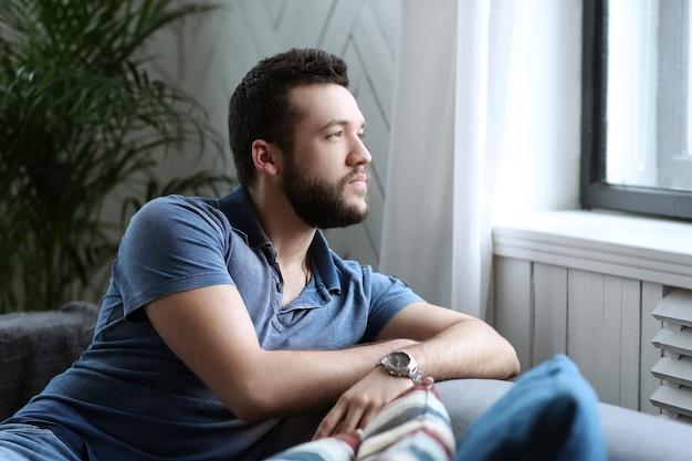 Homem bonito olhando para a janela do treinador
