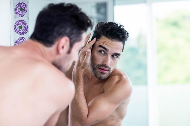 Homem bonito olhando para o cabelo no banheiro