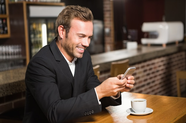 Homem bonito olhando para smartphone e tomando um café