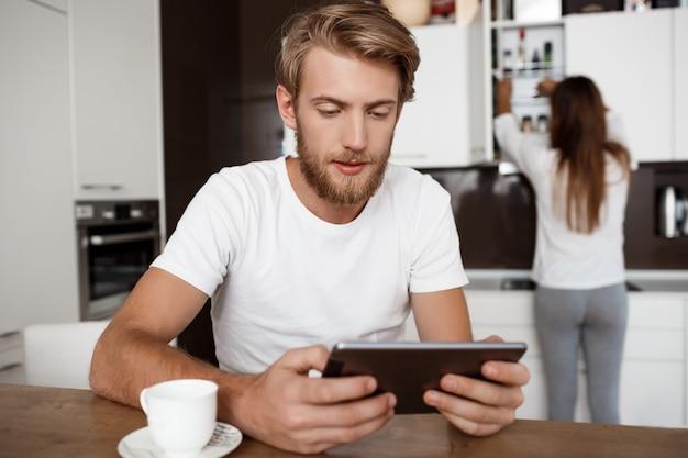 Homem bonito olhando para tablet. namorada na cozinha