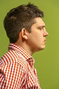 Homem bonito olhando surpreso e confuso isolado na parede verde