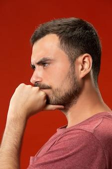 Homem bonito olhando surpreso e confuso isolado no vermelho