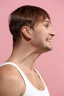 Homem bonito olhando surpreso isolado na parede rosa