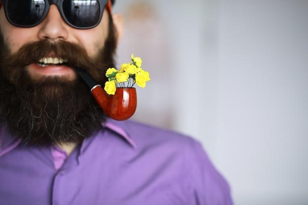 Homem bonito ou lenhador, hippie barbudo, com barba e bigode na camisa com cachimbo