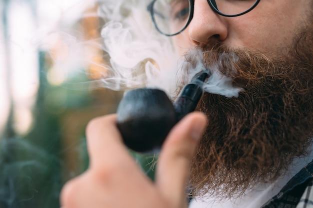 Homem bonito ou lenhador, hipster barbudo, com cachimbo de barba e bigode.