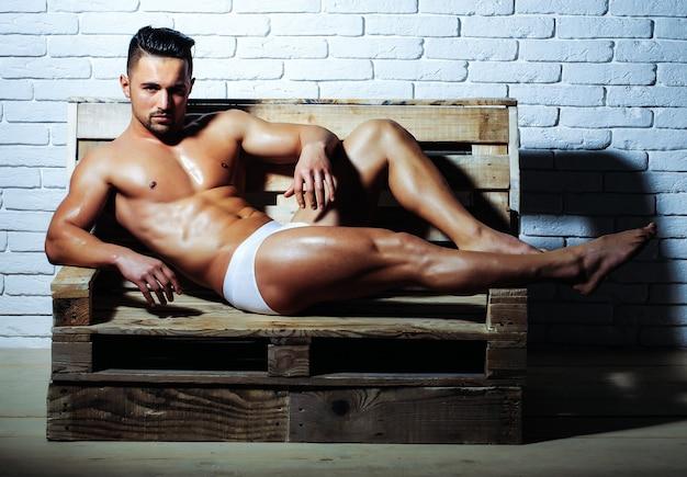 Homem bonito ou musculoso com corpo nu de torso muscular sexy com cueca de seis blocos em sofá de palete de madeira na parede de tijolo branco