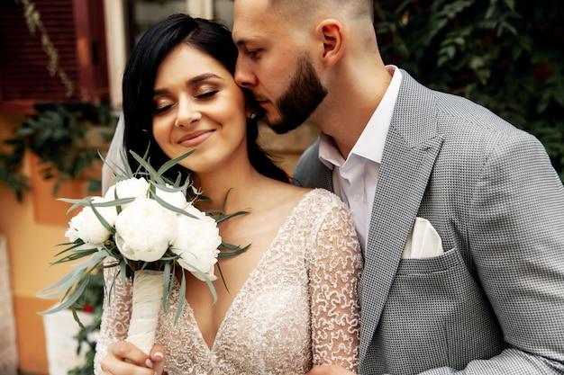 Homem bonito ou noivo afro-americano, abraçando a menina bonita ou noiva bonito com cabelo loiro lindo vestido de casamento sexy branco ao ar livre na rua da cidade turva fundo
