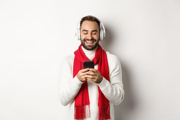 Homem bonito ouvindo músicas de natal em fones de ouvido sem fio, segurando o smartphone e sorrindo, em pé sobre um fundo branco
