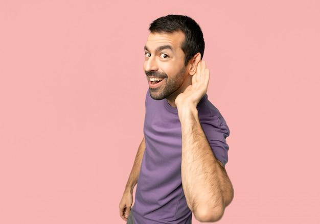Homem bonito ouvir algo, colocando a mão sobre a orelha no fundo rosa isolado
