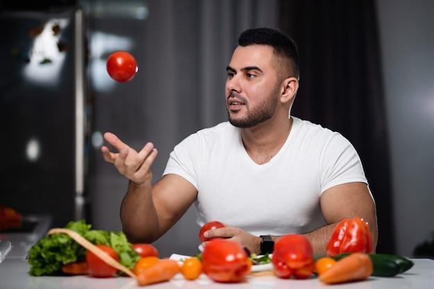 Homem bonito para comer comida vegetariana saudável em casa. o conceito de um estilo de vida saudável